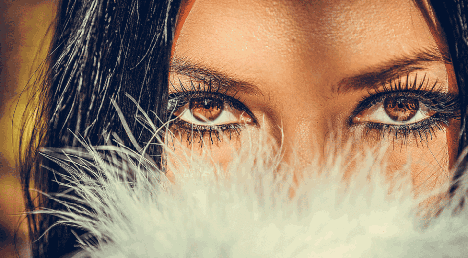 female model looking over a feather boa with bold eyes